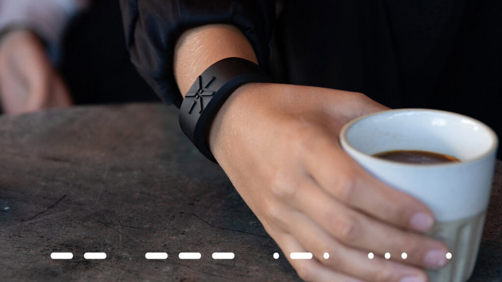 A hand is holding a cup with coffee and using Xtactor's wristband